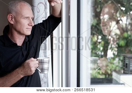 Portrait Of Good-looking Mature Caucasian Man Standing At Home With Cup Of Coffee And Looking Out Th