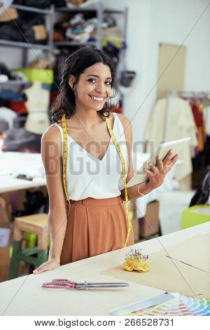 Portrait Of Smiling Young Tailor Standing Near The Workplace And Holding Touchpad While Working In C