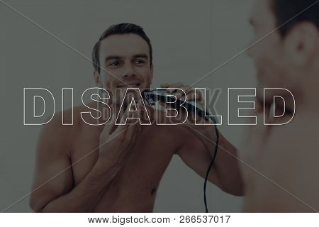 Disabled Man. Man Shaves With An Electric Razor. Man Looks At Himself In The Mirror. Man Is Smiling.