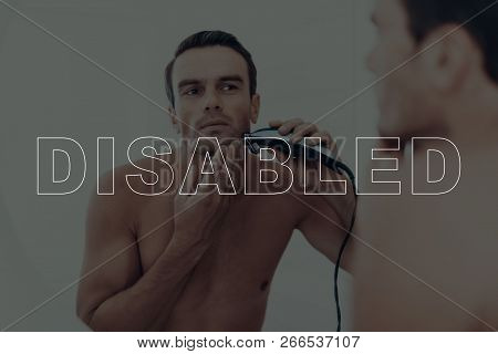 Disabled Man. Man Shaves With An Electric Razor. Man Looks At Himself In The Mirror. Man With Seriou