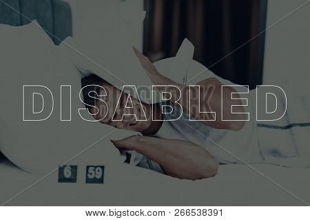 Disabled Man. Man Is Lying In Bed. Man Woke Up. Clock On Table Near Bed. 6:59 Time On Clock. Man Is