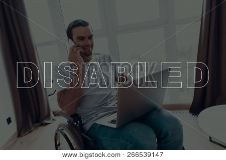 Disabled Man In A Wheelchair. Man Sits In Front Of Window. Man Using A Laptop. Man Talking On Mobile
