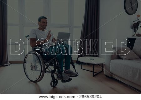 Disabled Man In A Wheelchair. Man Sits In Front Of Window. Man Have A Video Call. Video Call On Lapt