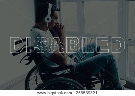 Disabled Man In A Wheelchair. Man Sits In Front Of Window. Man Looks Into Window. Man Listening Musi