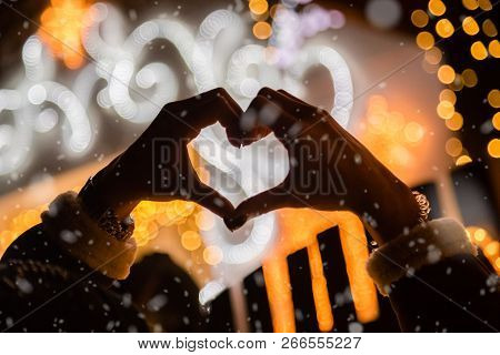 Rear View Of Female Making Heart Shape With Her Hands In Front Of House Decorated With Christmas Lig