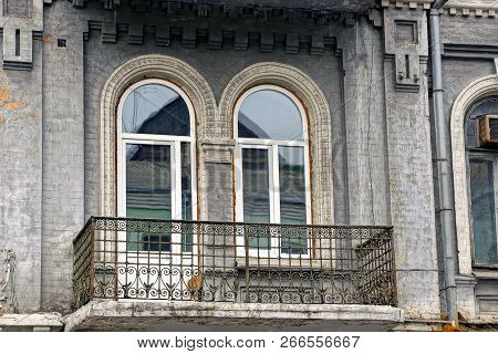 Old Iron Open Balcony On A Wall With A Glass Door And A Window