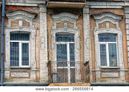 Old Iron Open Balcony On A Brick Wall With Windows And A Glass Door