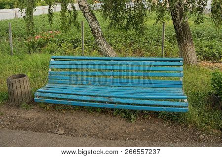 Old Blue Wooden Bench In The Green Grass Near The Trees
