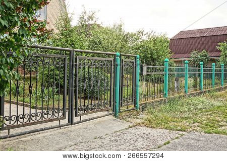 Black Iron Gates And Metal Fence Outside In Green Grass