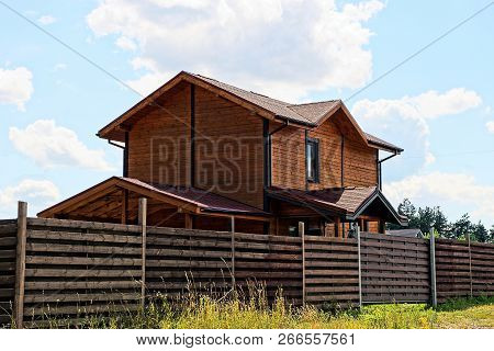 Brown Wooden House With A Window Behind The Fence In The Grass