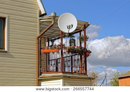 Round Satellite Dish On An Open Balcony With Flowerpots And Flowers On A Private House