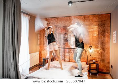 Modern Loft Bedroom Intreior With Bright Copper Wall And Motion Blurred Couple Fighting With Pillows