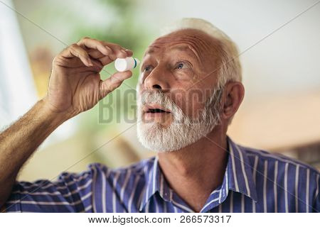 Elderly Person Using Eye Drops At Home