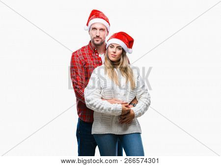 Young couple in love wearing christmas hat over isolated background with serious expression on face. Simple and natural looking at the camera.