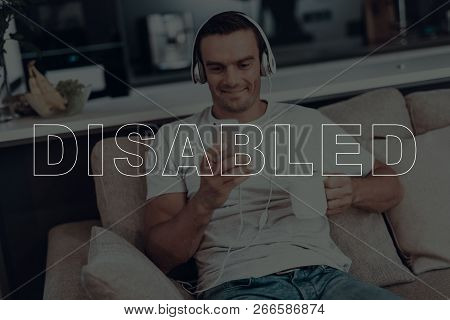 Disabled Man. Man Is Sitting On Sofa. Man Wearing A Headphones. Man Listening A Music. Music On Mobi