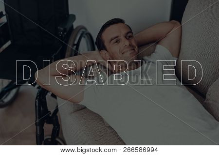 Disabled Man. Man Lying On Sofa. Wheelchair On Background Of Man. Man Is Relaxed. Adult Brunette Man