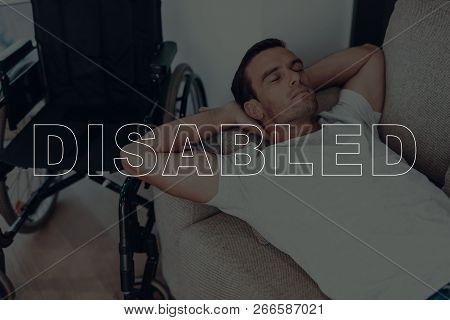 Disabled Man. Man Lying On Sofa. Wheelchair On Background Of Man. Man Is Relaxed. Man Is Sleeping. M