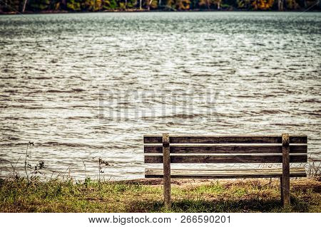 An Empty Park Bench Looks Over A Virginia Bay With Fall Colors Appearing On The Other Side.