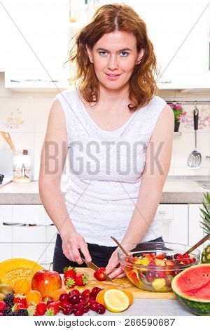 An Happy Young Housewife Making Fruits Salad