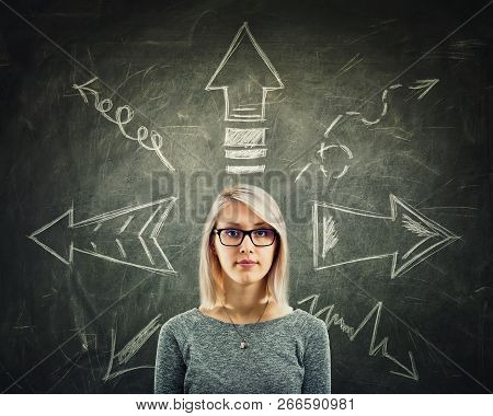 Young Woman Wearing Glasses In Front Of A Blackboard With Arrows Pointed To Different Directions. Di