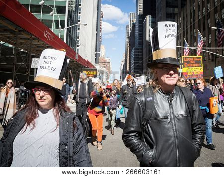 March For Our Lives: Marchers wear tophats that say Books Not Bullets and We're Done Hiding during the march to end gun violence on 6th Ave, NEW YORK MAR 24 2018.