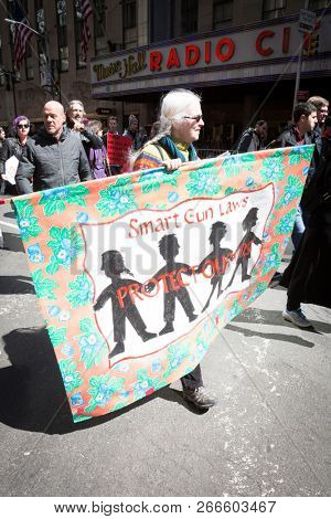March For Our Lives: A woman holds a banner that says Smart Gun Laws Protect Our Kids during the march to end gun violence on 6th Ave, NEW YORK MAR 24 2018.