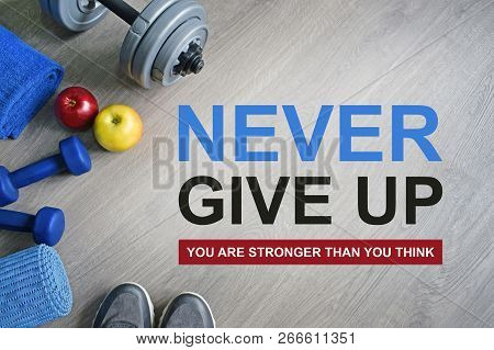 Never Give Up. You Are Stronger Than You Think. Fitness motivational quotes.Sport theme. Healthy and active lifestyle concept. Sneakers, dumbbells, apples and a workout mat on grey wooden background. poster