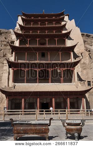Dunhuang, China - August 8, 2012: Tourists At The Entrance Of The Mogao Caves Near The City Of Dunhu