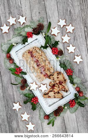 Stollen Christmas cake with gingerbread biscuits, winter holly, fir, acorns and mistletoe on rustic wood table background. Traditional Dutch and German fruitcake. Top view.