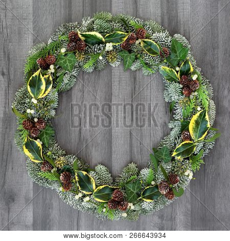 Winter and Christmas natural wreath with snow covered spruce pine fir, mistletoe, pine cones, cedar and ivy leaves on rustic grey wood  background.