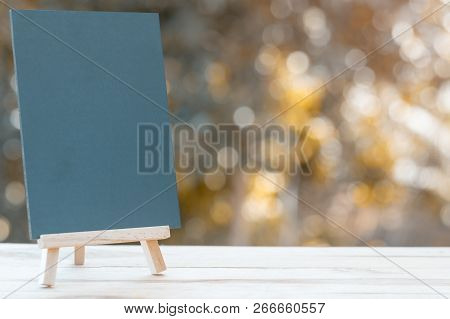 Image Of Empty Small Chalkboard On Wooden Easel Over Wooden Table Outdoor With Blurred Nature Backgr