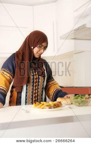 Красивые мусульманская женщина, стоя на кухне