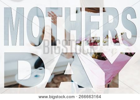 Mothers Day. Happy Family. Daughter Holding Present To Mother. Present Is Bouquet Of Flowers. Mother