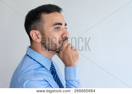 Serious Pensive Handsome Businessman Deep In Thoughts. Contemplative Young Man Touching Chin And Loo