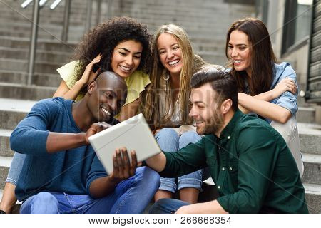 Multi-ethnic Group Of Young People Looking At A Tablet Computer Outdoors In Urban Background. Group