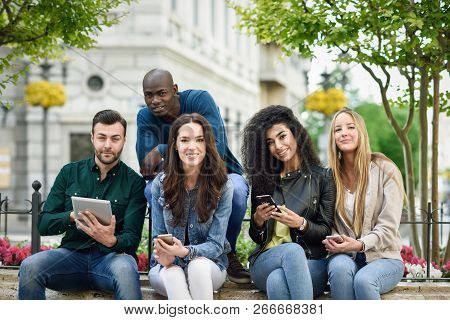 Multi-ethnic Group Of Young People Using Smartphone And Tablet Computers Outdoors In Urban Backgroun