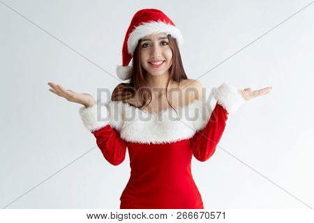 Portrait Of Smiling Girl In Santa Dress Shrugging Shoulders. Young Mixed Race Woman Wearing Christma