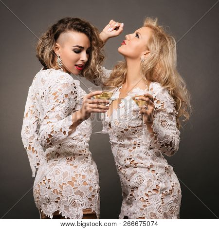 Two Beautiful Young Women Girlfriends Dance With Martini Glasses Isolated