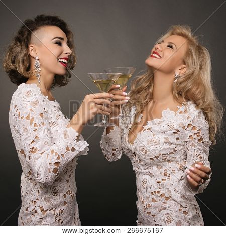 Two Beautiful Young Women Girlfriends In White Short Dress Celebrate The Holiday With Martini Glasse