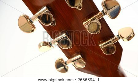 Music Closeup Guitar Headstock And Guitar Tuner On White Background.