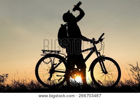 Silhouette Of A Man Drinking Water With A Bicycle At Sunset