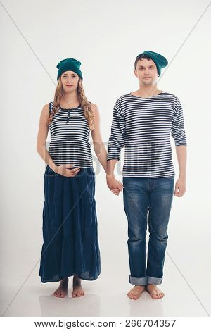 Couple Husband And Wife: Man And Pregnant Woman In Vests And Green Hats On White Background