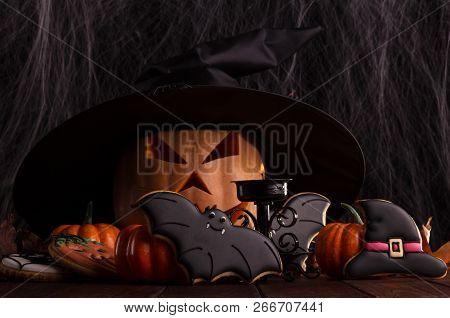 Festive Halloween Arrangement On A Dark Background. Pumpkin Jack, Black Witch Hat, And Spiders
