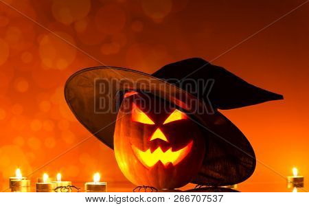 Pumpkin With Glowing Eyes And Candle On Bright Orange Background