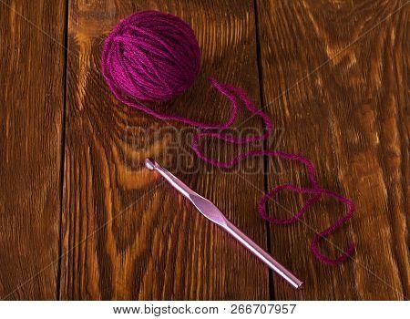 Skein Of Purple Wool Yarn And Crochet Hook On Dark Boards