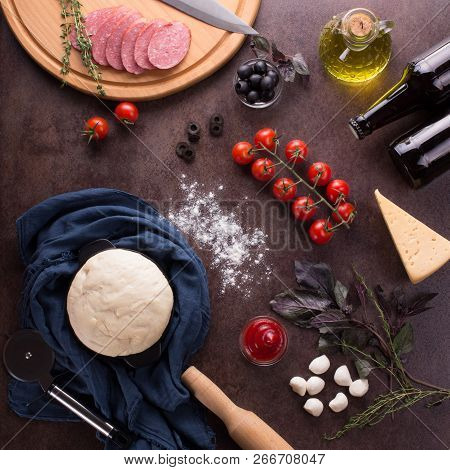 Top View. Ingredients For Making Flavorful Pepperoni Pizza On A Dark Background
