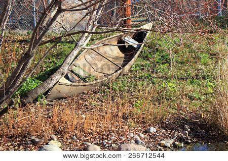 An Abandoned Wooden  Canoe Parked Along A Pond.