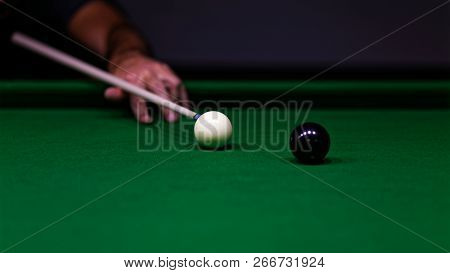 Man Trying To Hit The Ball In Billiard. Shallow Focus.