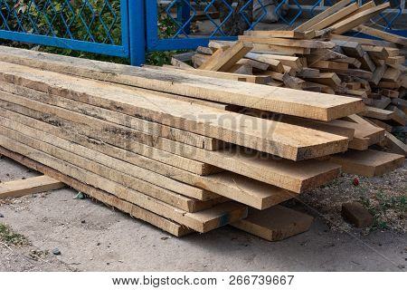 Pine Wood Timber Stack Of Natural Rough Wooden Boards On Building Site. Industrial Timber Building M
