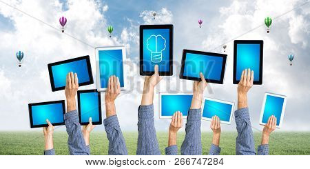 Set Of Tablets In Male Hands Against Nature Background And Balloons In Air